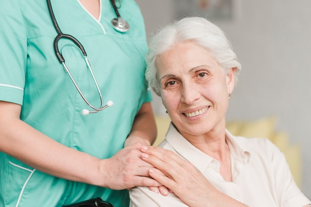 Smiling senior woman touching nurse hand on shoulder