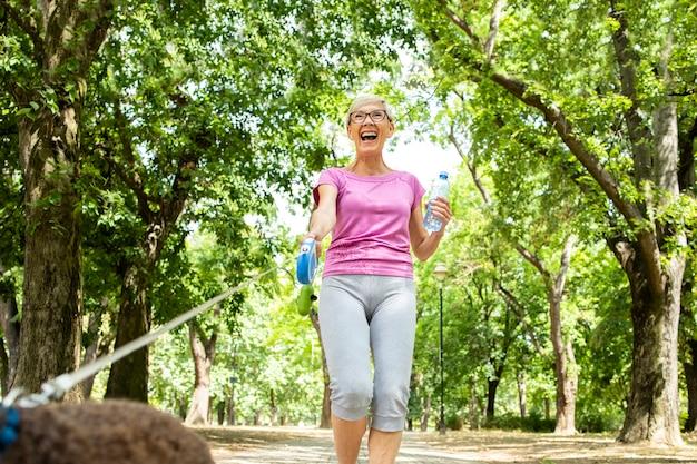 公園で犬を歩く年配の女性の笑顔。