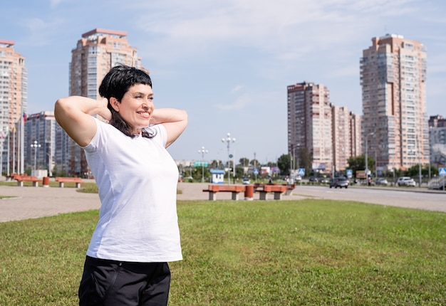都市のシーンで公園で屋外トレーニングの前にウォーミングアップ笑顔の年配の女性