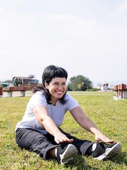 公園で屋外ストレッチをウォーミングアップ笑顔の年配の女性