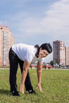 공원에서 야외 스트레칭 워밍업 웃는 고위 여자