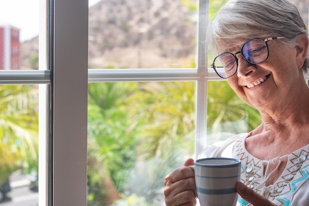 Smiling senior woman at the window holding a coffee cup