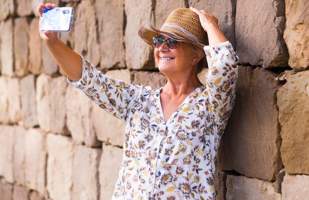 돌담에 서서 셀카를 찍기 위해 스마트 폰을 사용하여 밀짚 모자를 쓴 웃는 노년 여성