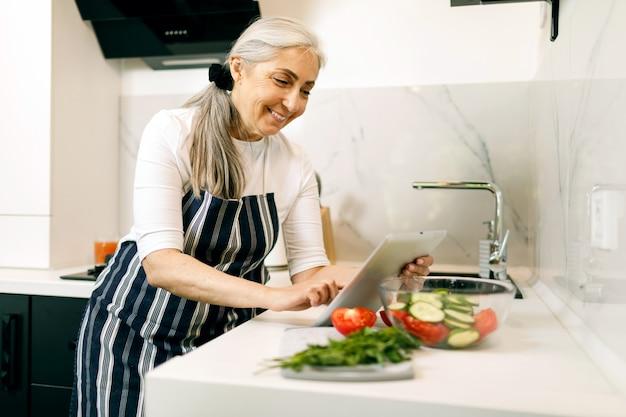 Усмехаясь старшая женщина с белыми волосами внутри в рисберме используя таблетку пока варящ на кухне