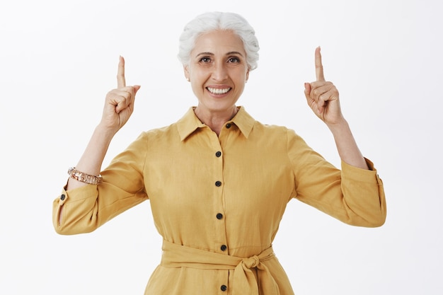 Smiling senior woman in yellow trenchcoat pointing fingers up