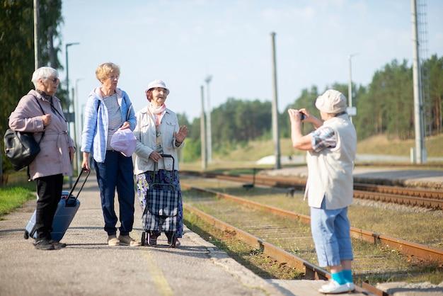 웃는 노인 여성이 기차 여행을 기다리는 플랫폼에서 사진을 찍습니다.
