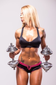Smiling sexy athletic woman pumping up muscules with dumbbells on gray