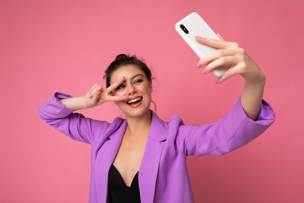Smiling sexy beautiful adult woman wearing purple suit taking selfie photo on the mobile phone
