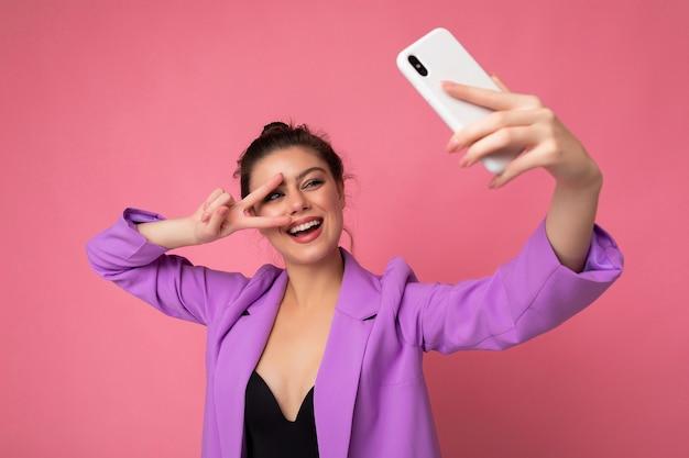 Улыбаясь сексуальная красивая взрослая женщина в фиолетовом костюме, делающая селфи фото на мобильном телефоне