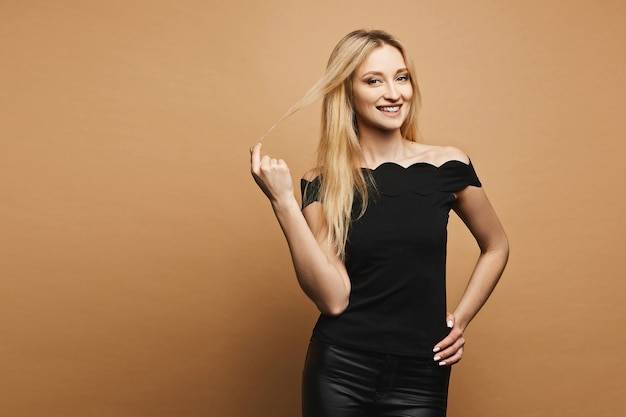 Smiling, sexy and beautiful blonde model girl with perfect body in black leather pants and black t-shirt adjusting her hair, smiling and posing at orange wall
