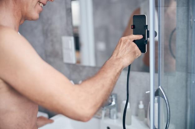 人差し指で携帯電話に触れる笑顔の上半身裸の男性