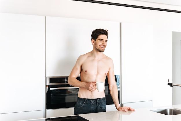 Улыбающийся мужчина без рубашки пьет кофе стоя