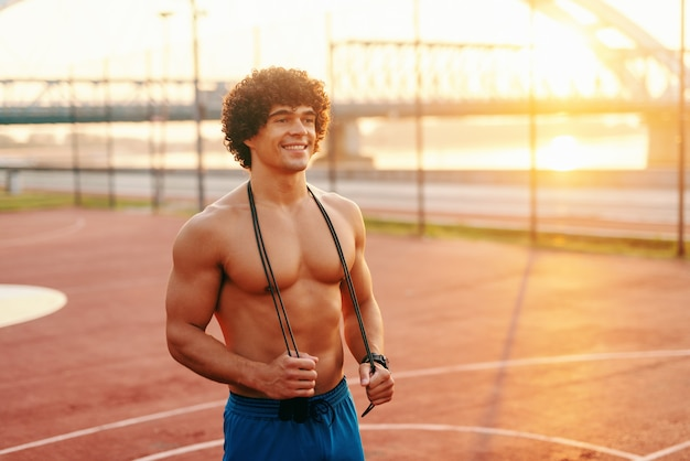 Улыбающийся человек без рубашки позирует со скакалкой на шее на площадке утром