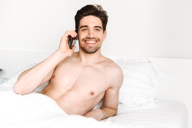 Улыбающийся мужчина без рубашки разговаривает по мобильному телефону