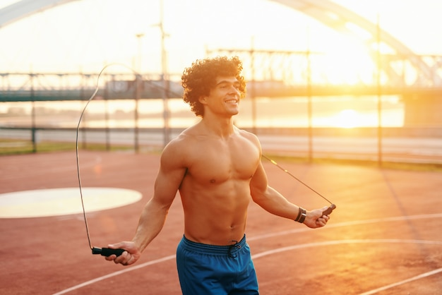 Smiling shirtless man with curly hair shipping rope on the court in the morning