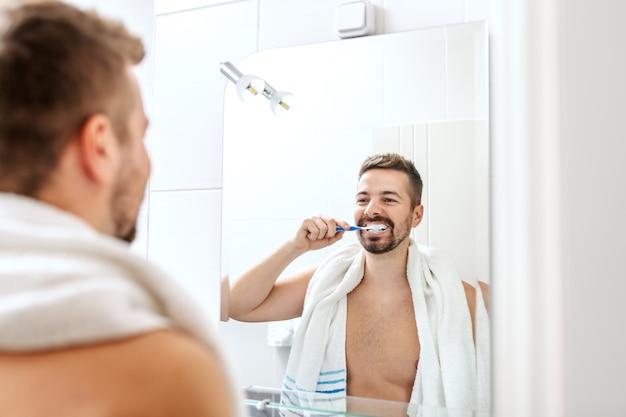 Улыбающийся мужчина без рубашки с полотенцем на шее, чистящий зубы, стоя перед зеркалом в ванной комнате.