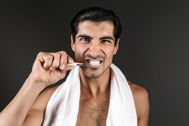 Улыбающийся мужчина без рубашки с полотенцем на плечах стоит изолированно и чистит зубы