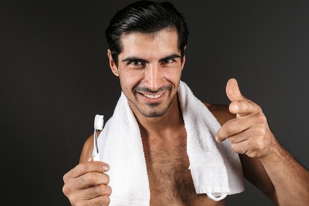 孤立して立って、歯ブラシを保持している彼の肩にタオルで上半身裸の男の笑顔