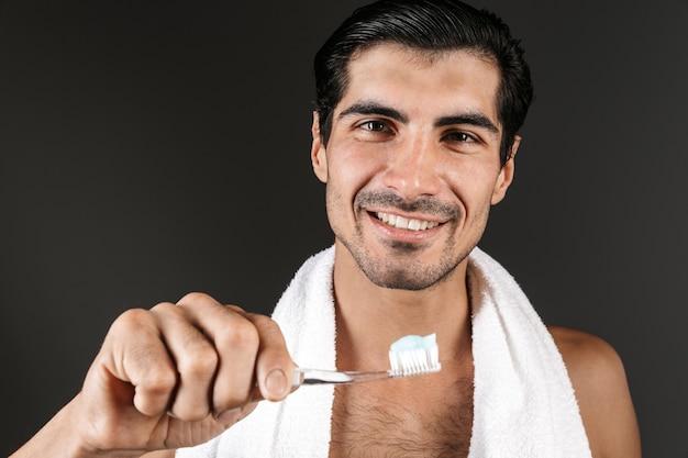Улыбающийся мужчина без рубашки с полотенцем на плечах стоит изолированно и держит зубную щетку