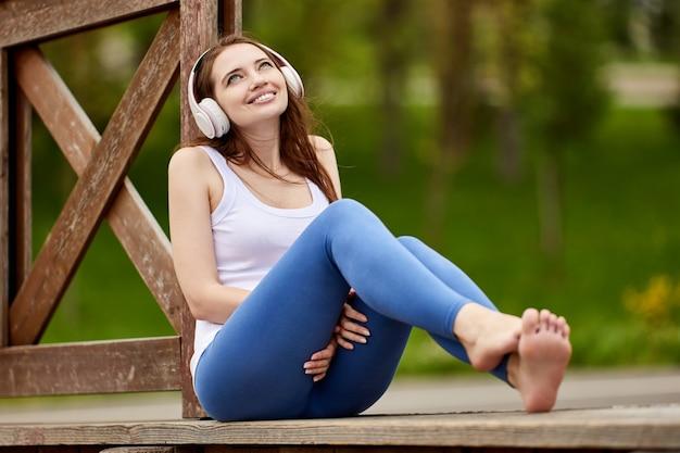 Улыбающаяся босая женщина в беспроводных наушниках слушает музыку в парке