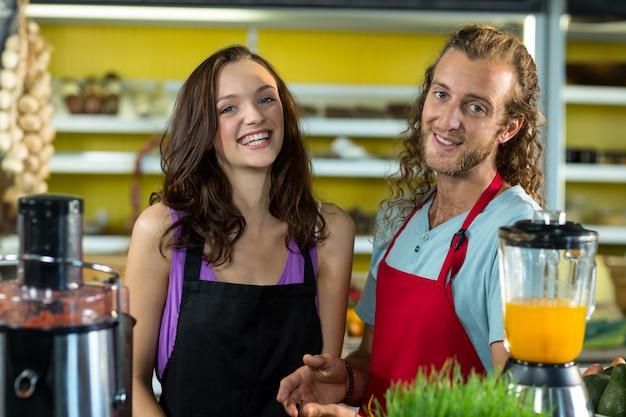 Улыбающиеся продавцы, стоящие вместе в продуктовом магазине