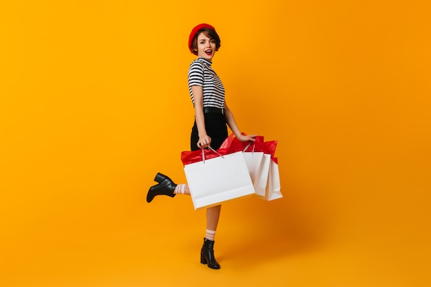 Sorridente donna shopaholic in piedi su una gamba sola