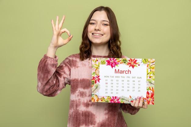 Sorridente che mostra gesto ok bella ragazza il giorno della donna felice che tiene il calendario isolato sul muro verde oliva