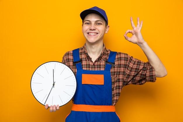 Sorridere che mostra un gesto ok giovane ragazzo delle pulizie che indossa l'uniforme e il berretto tiene l'orologio da parete