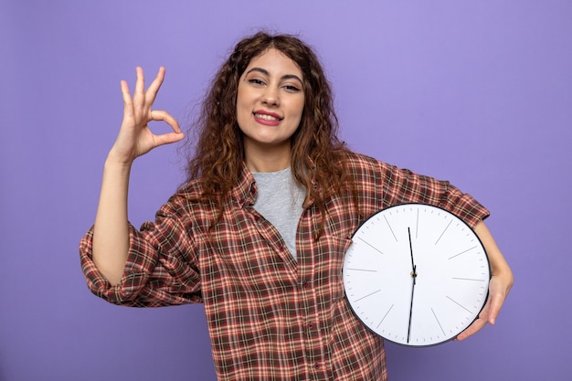 Sorridente che mostra gesto ok giovane donna delle pulizie che tiene l'orologio da parete