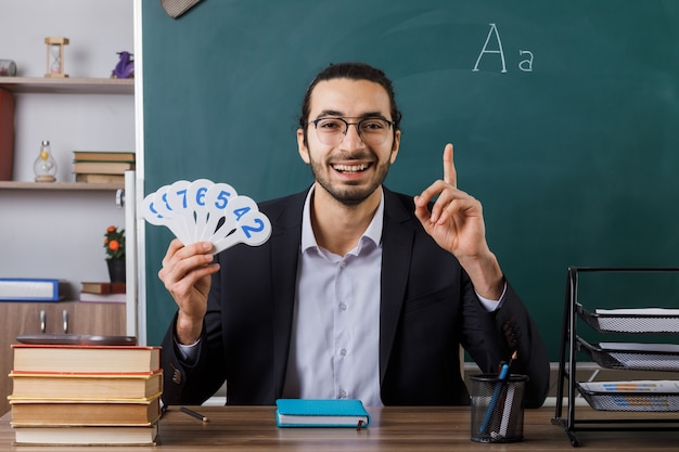 Sorridente che mostra un insegnante maschio con gli occhiali che tiene in mano un numero di fan seduto al tavolo con gli strumenti della scuola in classe
