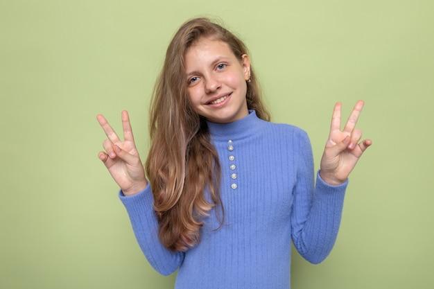青いセーターを着て平和ジェスチャー美しい少女を見せて笑顔