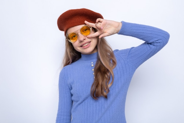 平和のジェスチャーを示す笑顔帽子と眼鏡をかけている美しい少女