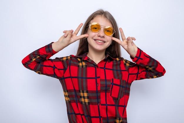 赤いシャツとメガネを身に着けている平和ジェスチャー美しい少女を示す笑顔