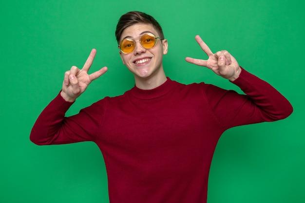 緑の壁に分離された眼鏡をかけている平和ジェスチャー若いハンサムな男を示す笑顔