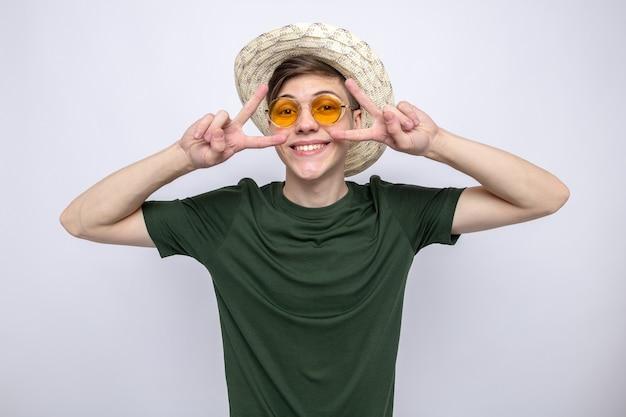 白い壁に隔離された眼鏡と帽子をかぶって平和ジェスチャー若いハンサムな男を示す笑顔