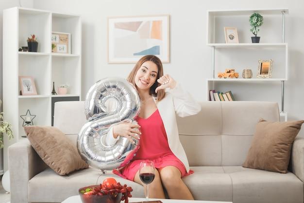 거실 소파에 앉아 8번 풍선을 들고 행복한 여성의 날에 엄지손가락을 아래로 내리고 웃는 여성