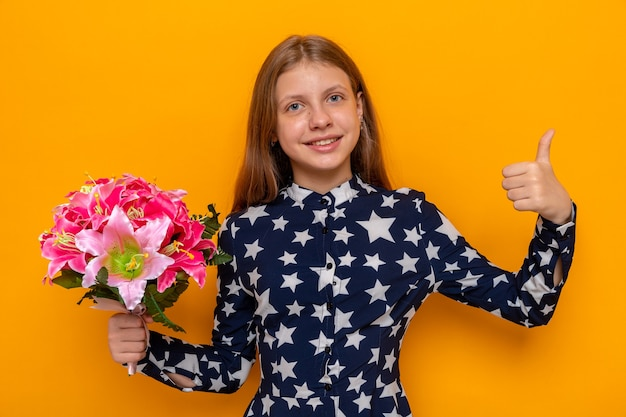 Smiling showing thumb up beautiful little girl holding bouquet