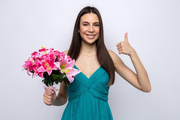 흰 벽에 고립 된 꽃다발을 들고 아름 다운 젊은 여자를 보여주는 엄지손가락을 웃 고
