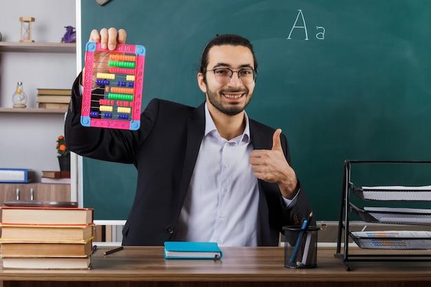 Sorridente che mostra pollice in su insegnante maschio con gli occhiali che tiene l'abaco seduto al tavolo con gli strumenti della scuola in classe