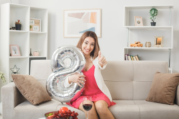 Smiling showing thumb up woman on happy woman's day holding number eight balloon sitting on sofa in living room