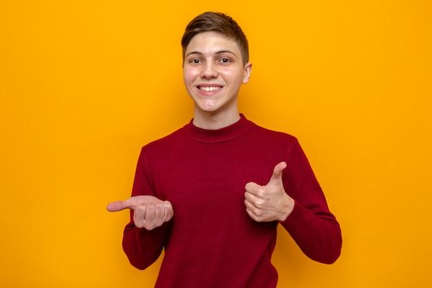 Улыбающийся показывает палец вверх молодой красивый парень в красном свитере