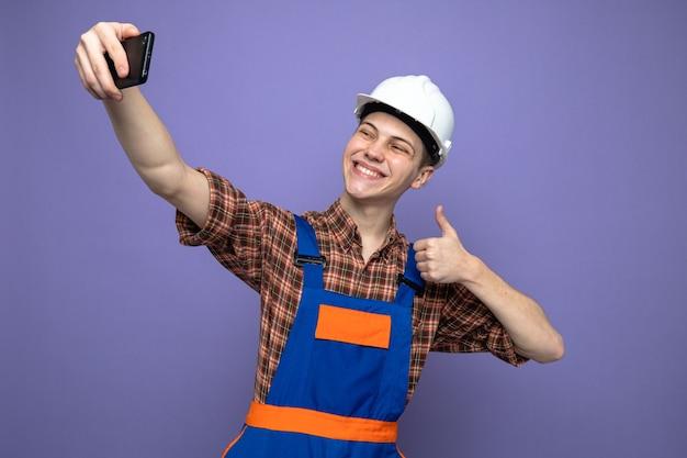 Sorridere mostrando pollice in su il giovane costruttore maschio che indossa l'uniforme prende un selfie