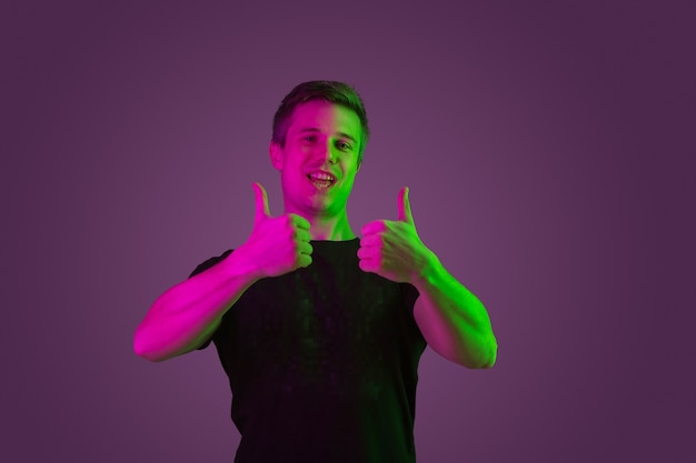 Smiling, showing thumbs up. caucasian man's portrait on purple studio background in neon light. beautiful male model in black shirt. concept of human emotions, facial expression, sales, ad.
