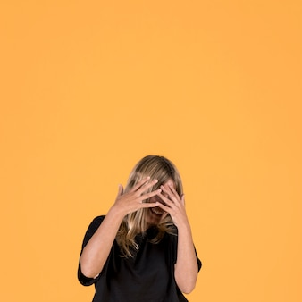 Smiling shy woman covering her face with finger