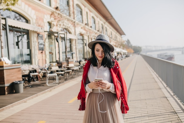 Smiling shy woman in hat standing on the street and looking at phone