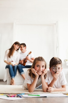 Smiling sibling lying on rug carpet looking at camera while their parent sitting on sofa