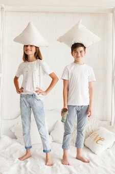 Smiling sibling standing with pillow on their head in bedroom