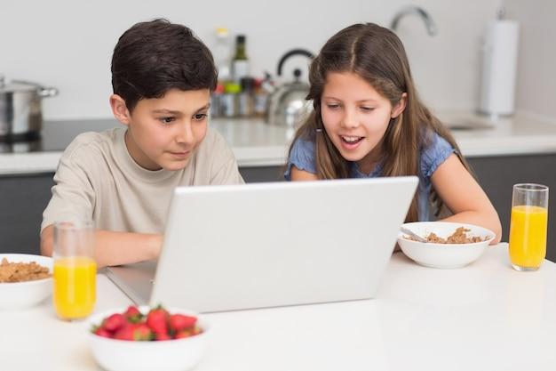 부엌에서 노트북 동안 아침 식사를 즐기는 웃는 형제