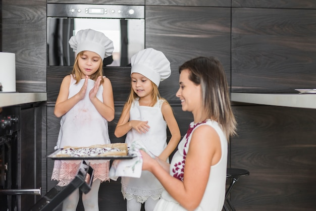 Smiling siblings looking at mother holding fresh baked cookies in tray