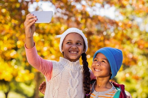 Smiling siblings taking selfie at park